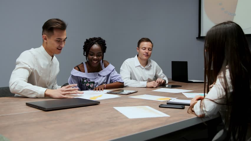 A group of creative multi-ethnic managers disassemble at the meeting of the board of directors in the conference hall the graphs of profit for the last year in the firm. The boss of an African   Shutterstock HD Video #1009936052