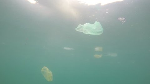 Plastic pollution in ocean. Environmental problem carrier bags,straws,cups and bottles dumped in sea.