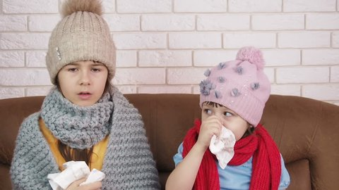 Colds flu. Sick children with a handkerchief for the nose. Little girls sneeze.