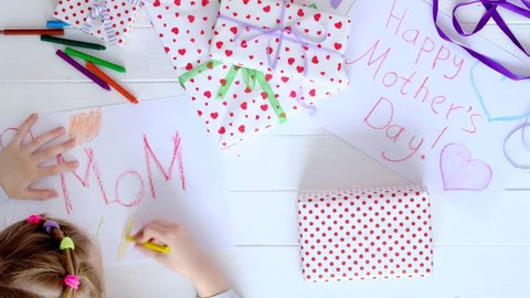 Little girls drawing greeting cards and wraps gifts with purple ribbon for mother's day