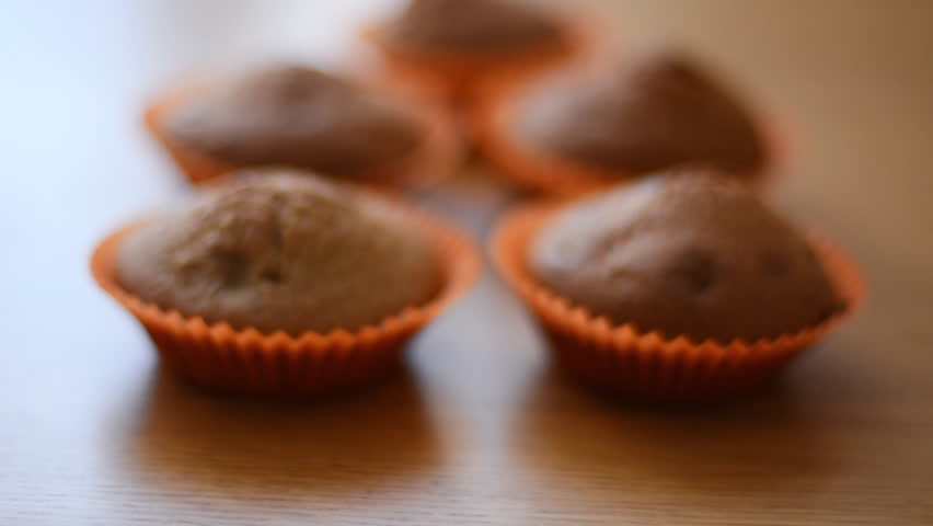 Chocolate cupcakes in paper orange cups on a wooden table. | Shutterstock HD Video #1009958162