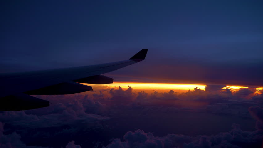 COPY SPACE POV: Large airplane wing flying through beautiful purple and orange sky. Commercial plane flying at cruising altitude passes colorful twilight. Cool view from the window seat of an airplane