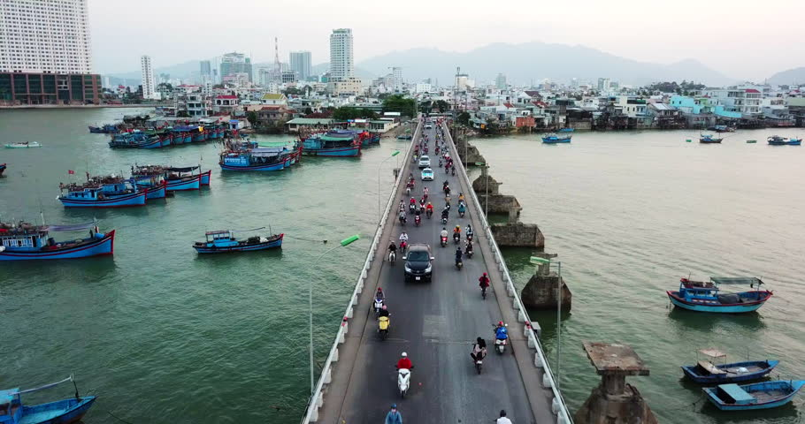 AERIAL 4K: Motorcycle and car traffic in Nha Trang Bridge, Vietnam. Boats near the bridge. CIty buildings in the background