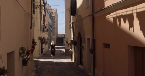 ALGHERO, SARDINIA, ITALY – JULY 2016 : Video shot of beautiful blonde girl walking in narrow street in central Alghero on a sunny day