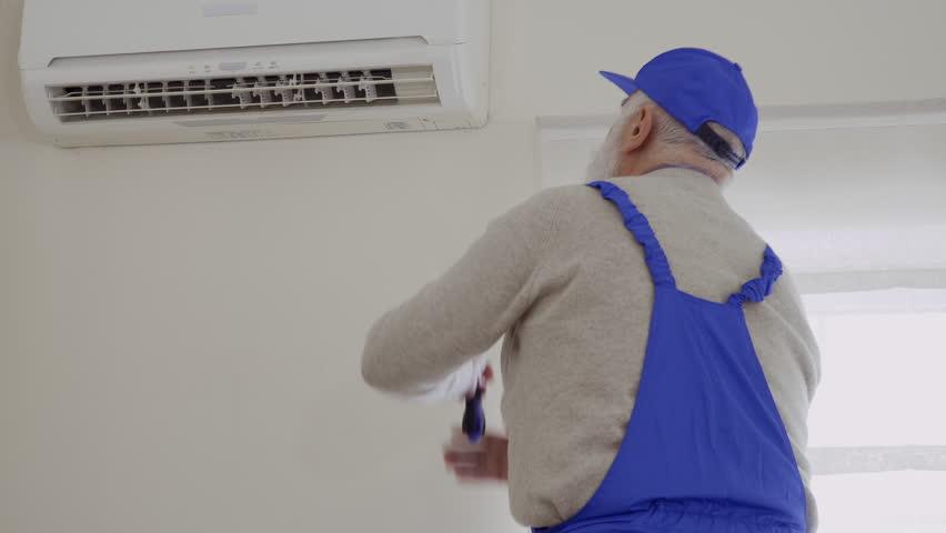 Senior man in blue overalls repair air conditioning