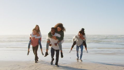 Group Of Friends Having Piggyback Race On Winter Beach Together