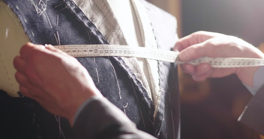 Portarit of a tailor while making a business suit using the tape measure. Concept: Fashion, tailoring, shop