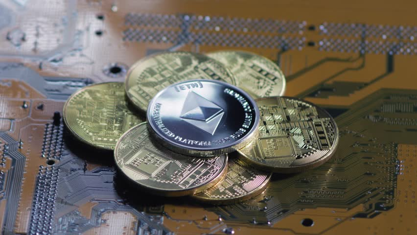 Crypto currency etherium. ethereum coin on exchange charts. e-currency etherium on the background of the circuit board | Shutterstock HD Video #1010018042