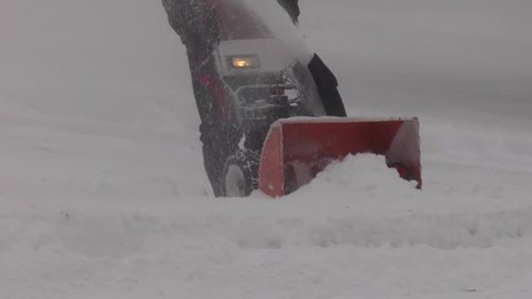 snowblowing in the winter blizzard front angle