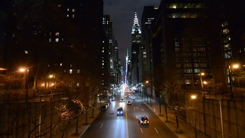 View down 42nd Street towards Grand Central at night from Tudor City district, New York. The Chrysler building can be seen in the background as vehicles drive along the road.