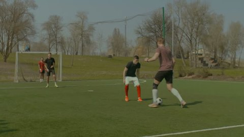 Young soccer goalie saving goal during football training match. Skillful striker dribbling , getting past defender and shooting on goal while playing football match on sports field. Stabilized shot.