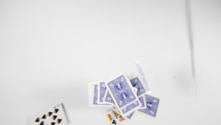 slow motion falling deck of cards onto white surface. Casino or gabling playing cards floating down. Thrown magic trick.