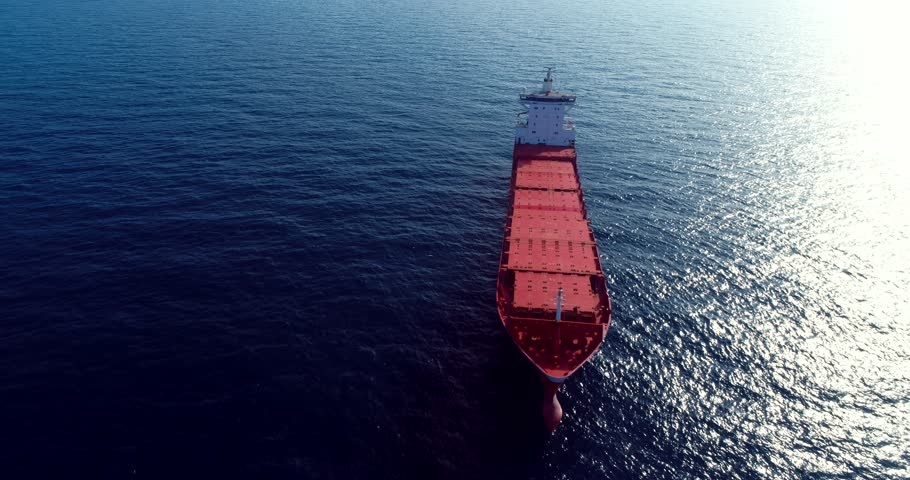 367 Aerial 4k cinematic with a  Large red Bulk ship .  Orbiting a coal ship out on the open sea
