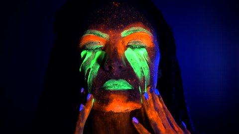 Portrait of girl smears and rubs fluorescent paint under eyes. Dye glowing near UV black light. Woman with braids in neon light. Night club, party, halloween psychedelic concepts.