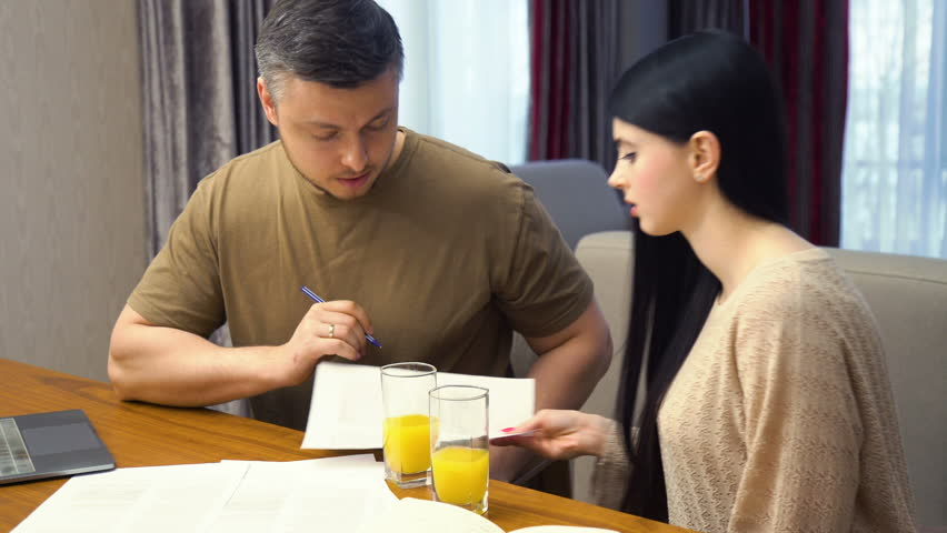 Family communication. home business. documents paperwork discussion. forms filling out. man and woman drinking juice and talking | Shutterstock HD Video #1010108522