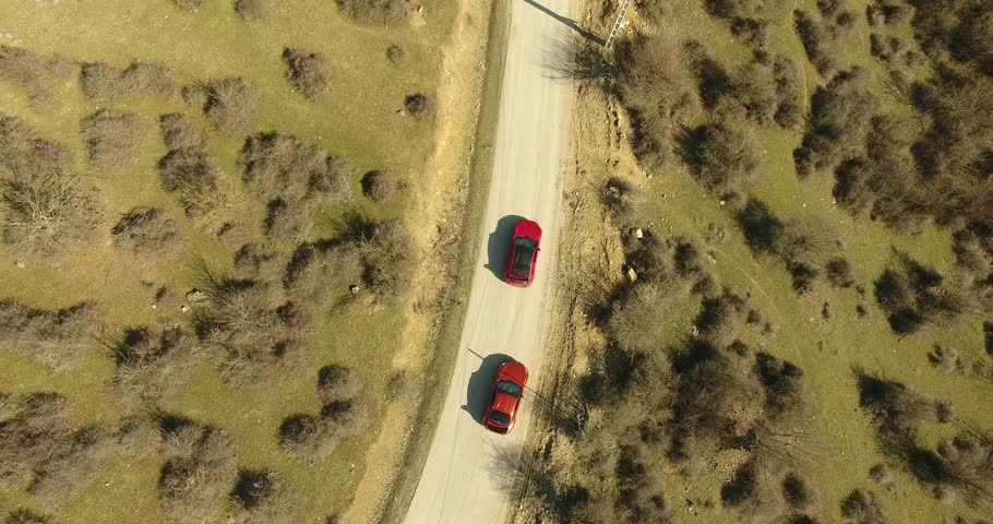 Aerial bird eye view shot of two super sport cars riding on nature road Super cars red natural sun light offroad sunny day riding on road in nature near trees no color correction ,raw footage