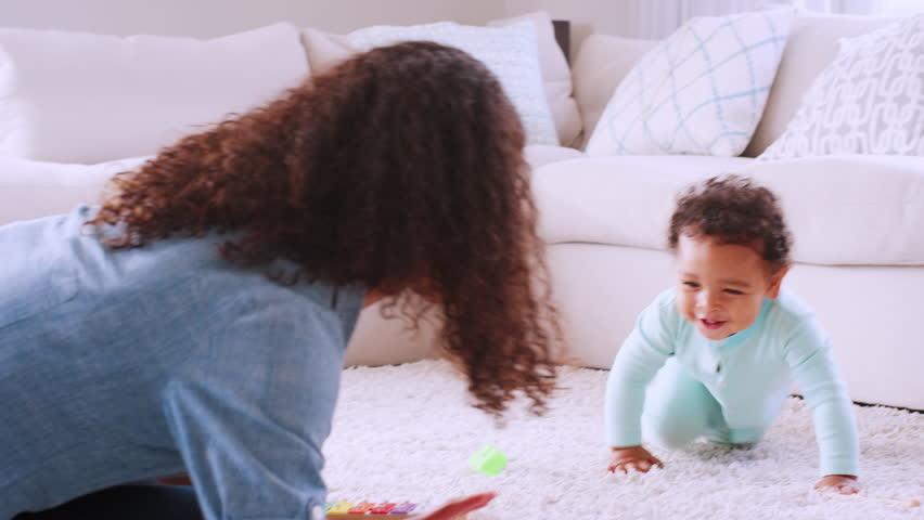 Black toddler boy crawling around his kneeling young mother