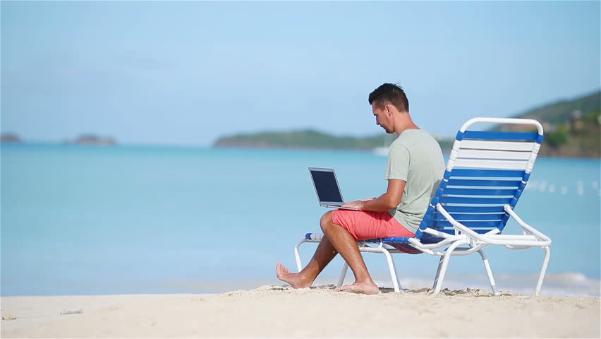 Young man with laptop on tropical beach. Man sitting on the chaise-lounge with computer working and relaxingthe same time | Shutterstock HD Video #1010155622