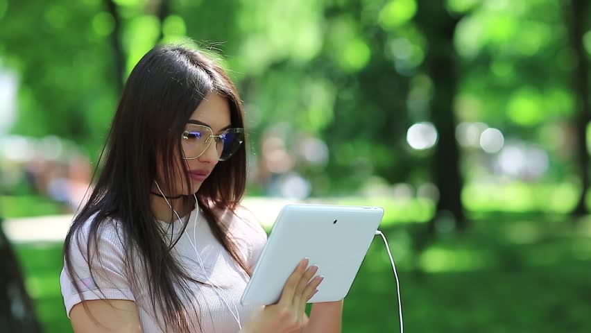 Girl in glasses uses tablet pc. Beautiful woman with white tablet computer, female with tablet pc | Shutterstock HD Video #1010156642
