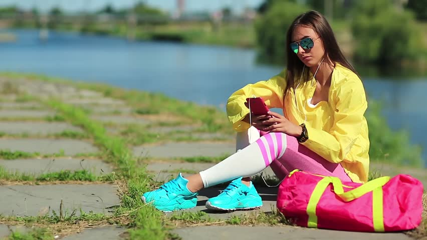 Sportswoman sits near pond and uses smartphone. Pretty girl in yellow sports jacket and sunglasses sits near lake and uses mobile phone. Woman in sportswear with cell phone | Shutterstock HD Video #1010156672