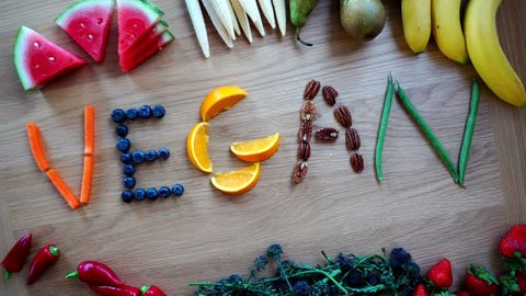 Vegan Word Spelt In Fruit And Vegetables Letters Overhead Time-Lapse, 4K Healthy Eating On Wood Table Preparations.