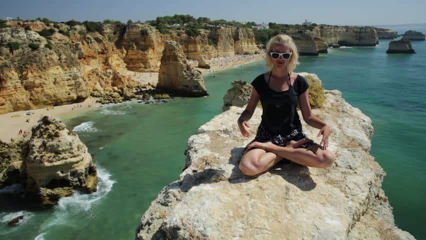 Serene meditation yoga. Blonde tourist woman meditating in lotus position on promontory above scenic Praia da Marinha. Meditating female on cliffs of Marinha Beach. Tourism in Algarve Coast, Portugal.