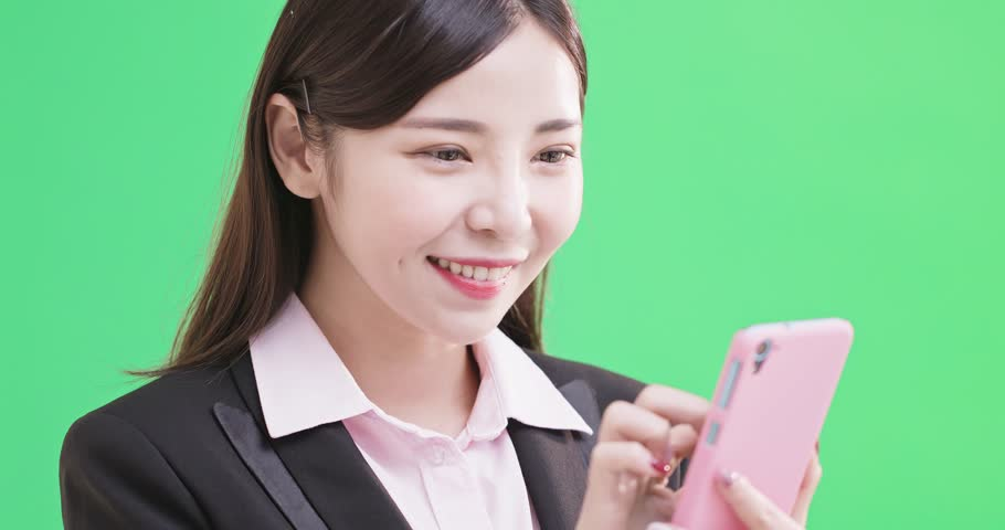 Businesswoman use phone on the green background | Shutterstock HD Video #1010174702