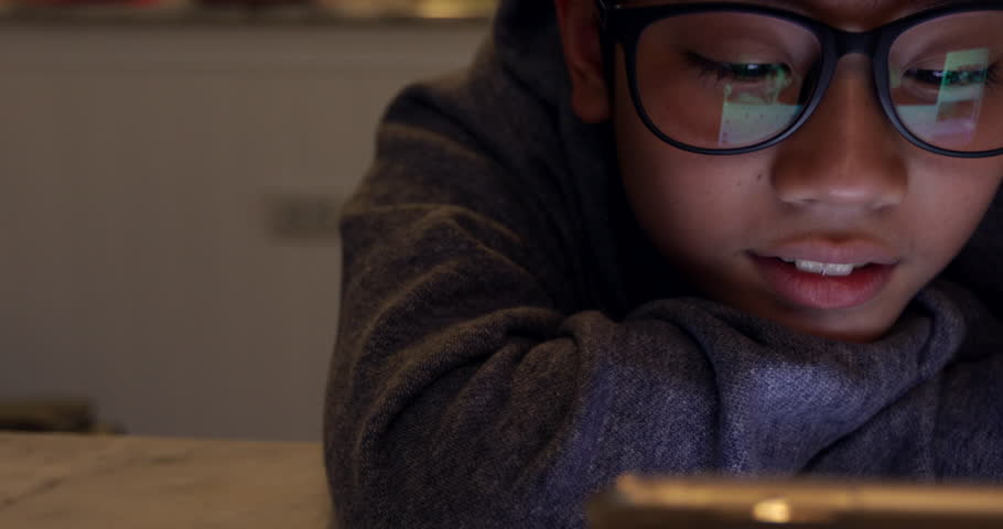 Cute asian boy wearing eye glasses and using tablet computer ,Young teenage boy playing games on digital tablet . | Shutterstock HD Video #1010177072