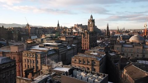 4K aerial drone video of a clock tower, castle, and ancient buildings in Edinburgh, Scotland during the morning