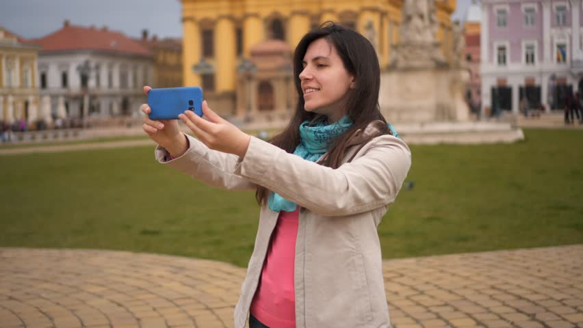 Girl taking selfies at Timisoara. Young brunette woman making selfies with her phone camera in city of Timisoara, Romania.