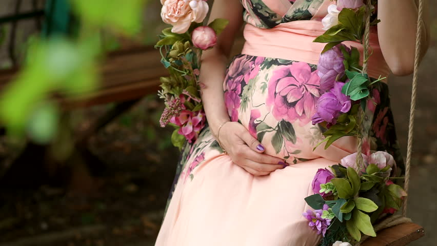 A young pregnant girl in a beautiful dress walking in the summer in the Park among trees and flowers. Closeup of the belly of a pregnant girl in a beautiful dress. Slow motion.   Shutterstock HD Video #1010185772