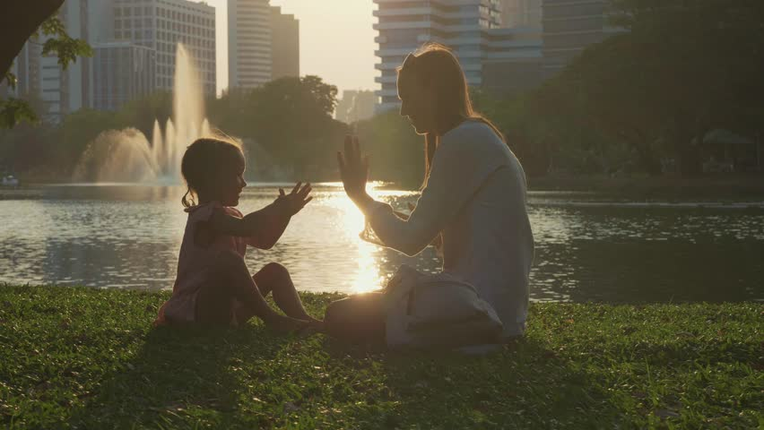 Mother having fun with her little cute daughter. Mom and child playing clapping game in the park with skyscrapers on the background at sunset and mother start tickling daughter in slow motion