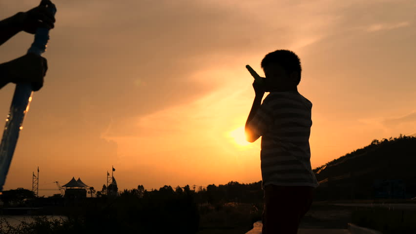 Young girl and boy playing with soap bubbles against sunset, slow motion    Shutterstock HD Video #1010196812