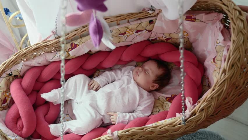 Cute newborn baby sleeping in swinging wattled cradle   Shutterstock HD Video #1010198852