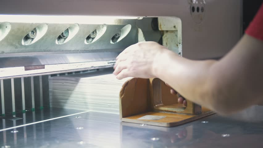 Hands of worker takes away reams of paper from cutting maschine   Shutterstock HD Video #1010200142