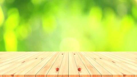 Wood table top on blur natural green leaves background.