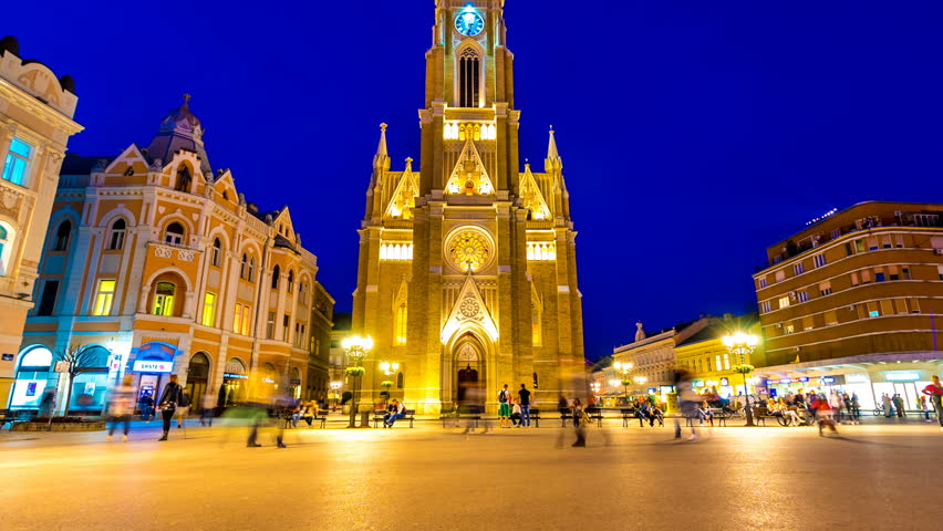 NOVI SAD, SERBIA - MAY 22: Time-lapse view on the Cathedral of the city at night as People pass by on May 22, 2017 in Novi Sad, Serbia.