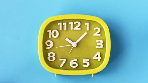 Green clock with white numbers and arrows on blue background, Time Lapse