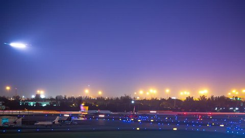 Vibrant Commercial Aviation Airport Airfield Action Timelapse at Night with Light Streaks from Jet Airliners Landing and Taking off in a Colorful Sky