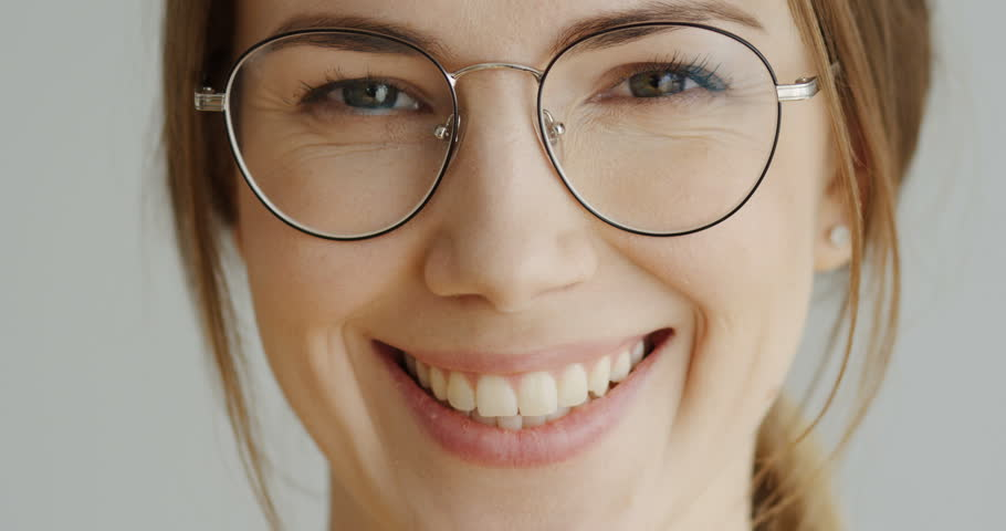 Close up of the woman's face in glasses with fair hair looking straight in the camera and smiling on the white wall background. Portrait. Inside | Shutterstock HD Video #1010214452