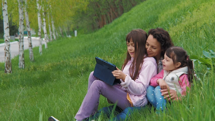 Family with a tablet on the nature. Children with mom in the park with a gadget. | Shutterstock HD Video #1010215472