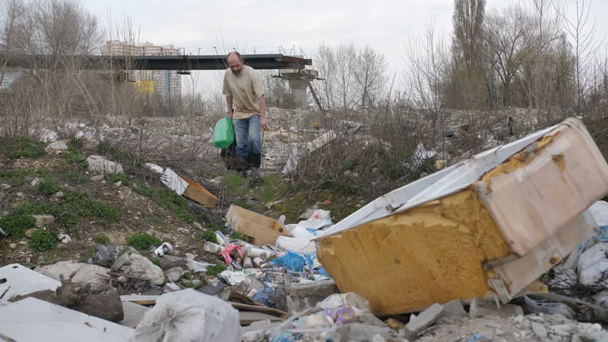 Mature man in dirty clothes walking on garbage dump site scavenging for plastic to recycle. Bearded omeless man holding bin bags searching for plastic at illegal city landfill.