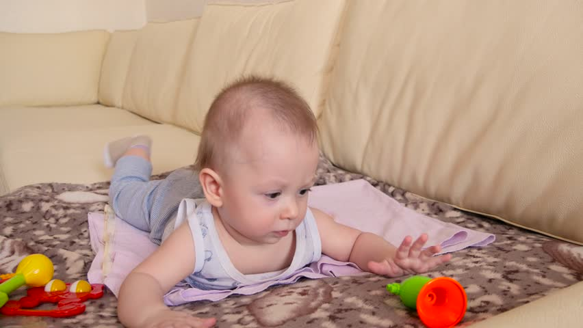 Cute baby boy, playing with toys in a living room, lying down on the sofa