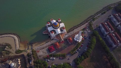 Top down aerial view footage - View of a White Floating Mosque, The Melaka Straits Mosque, located on the man-made Malacca Island near Melaka City, Melaka, Malaysia. Clip record by drone