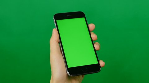 Businesswoman using a blank green screen mobile phone on green background. Front view.