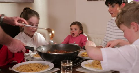 Family are enjoying a bolognese at home. The father is serving it from a pan.