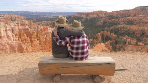 Lover couple in cowboy hats sit, hugging, on log bench over the edge cliff and look at a beautiful panorama of trees and rocks of the Bryce Canyon. Experience the harmony and peace of mind with peace