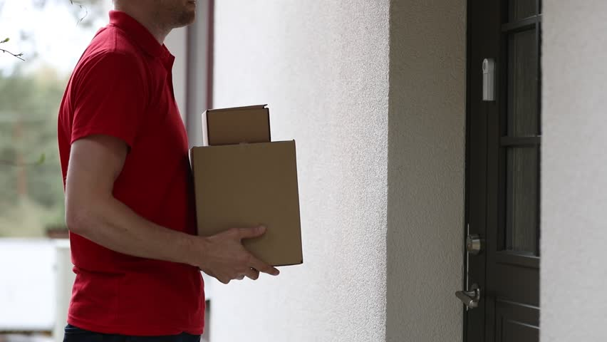Delivery service courier ringing the house doorbell with boxes in hands | Shutterstock HD Video #1010247782