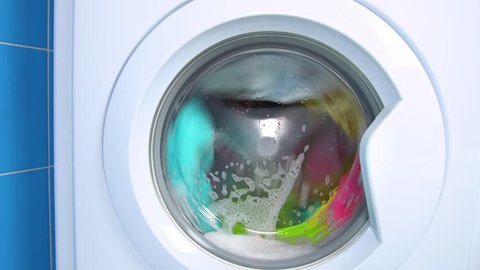 Washing machine washes colored clothing and sheets. Cylinder spinning.