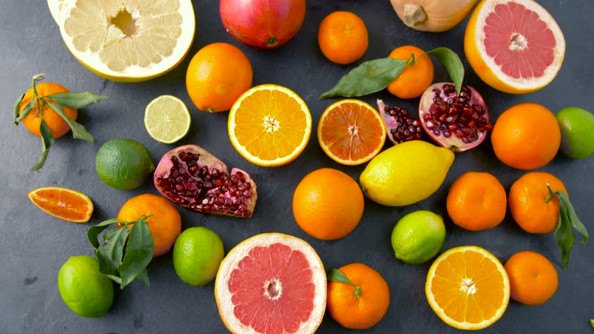 Food, healthy eating and vegetarian concept - close up of citrus fruits on stone table